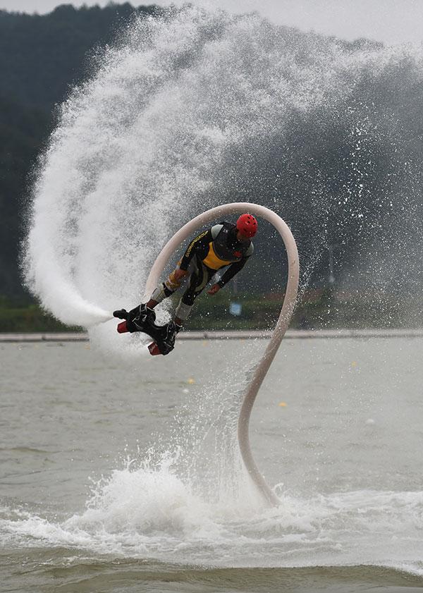 """中国摩托艇青年队队员在表演""""水上飞人""""空中翻腾特技。"""