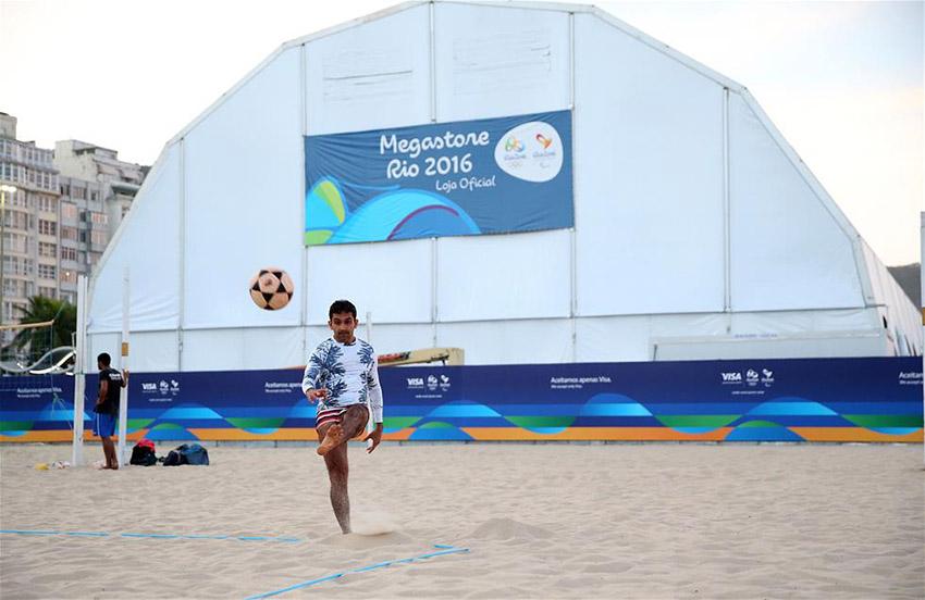 图为7月8日,一名男子在里约科帕卡巴纳海滩一处奥运特许商店外踢沙滩足排球。