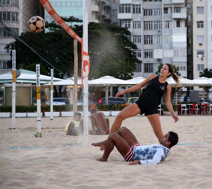 7月8日,人们在里约科帕卡巴纳海滩上踢沙滩足排球。里约奥运会沙滩排球的比赛场地就坐落在这片海滩。