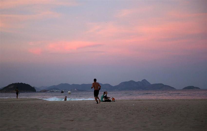 图为7月8日,一名男子在里约科帕卡巴纳海滩上带球跑步。里约奥运会沙滩排球的比赛场地就坐落在这片海滩。