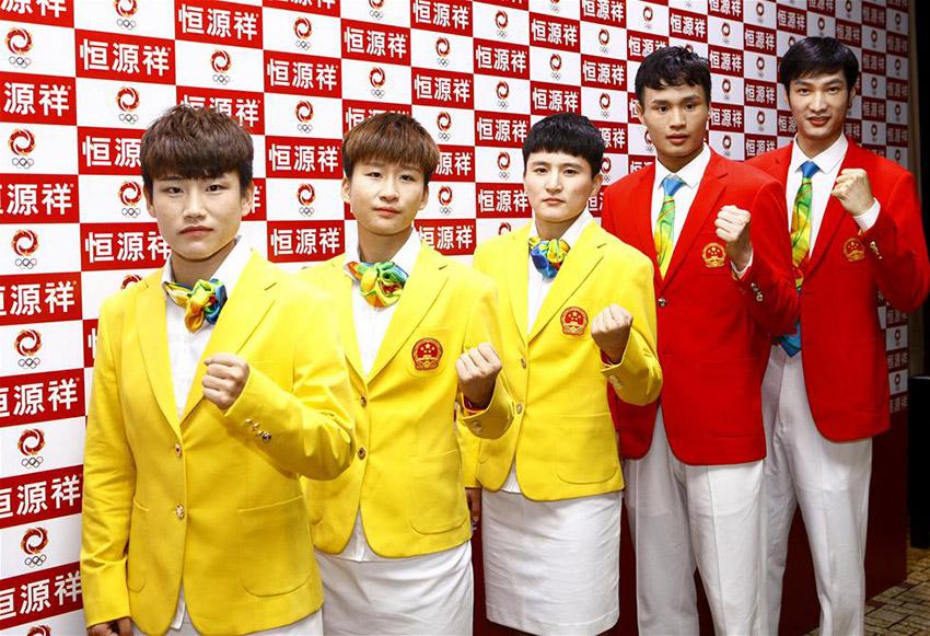 女足队员庞丰月、娄佳惠、王珊珊和击剑选手陈海威、雷声(从左到右)在仪式上身着奥运礼服合影。