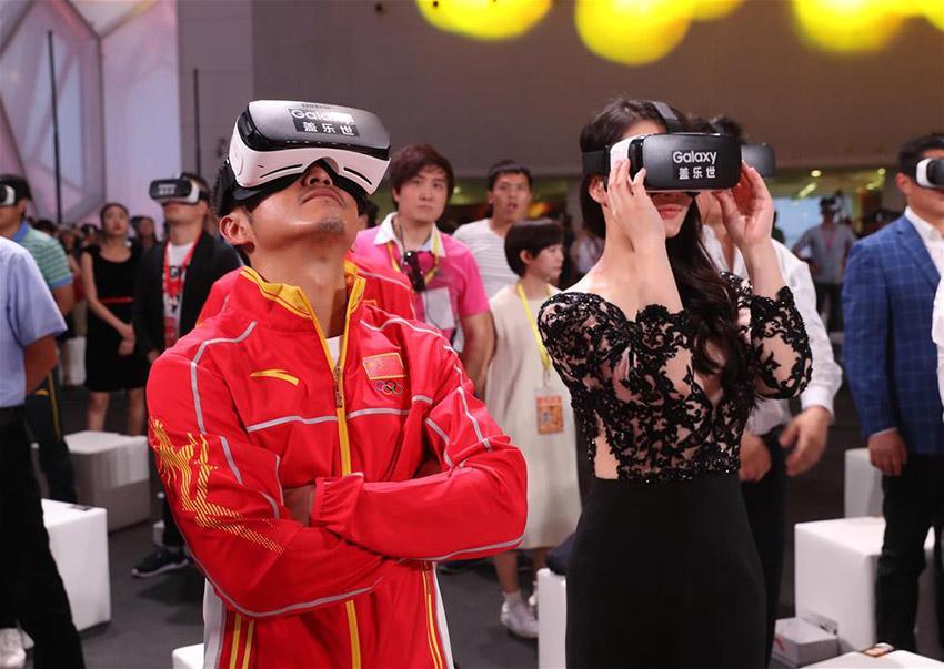 奥运冠军邹市明(左)与妻子冉莹颖在发布仪式上用VR技术观看冠军龙服发布视频。