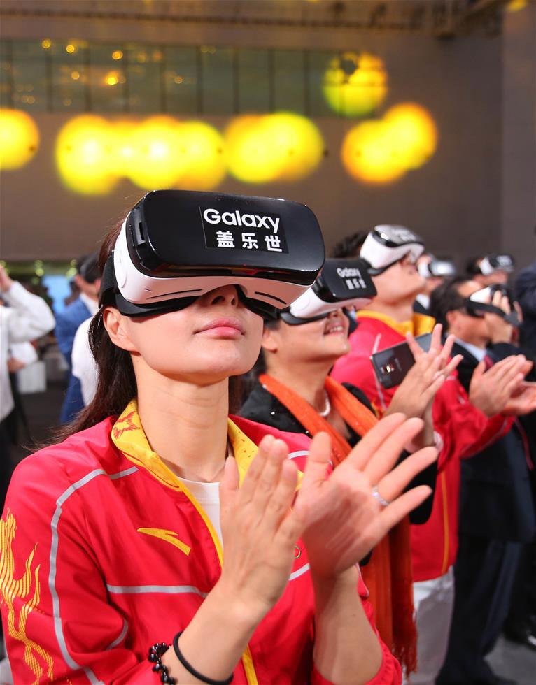 奥运冠军郭晶晶(前)在发布仪式上通过VR技术观看冠军龙服发布视频。