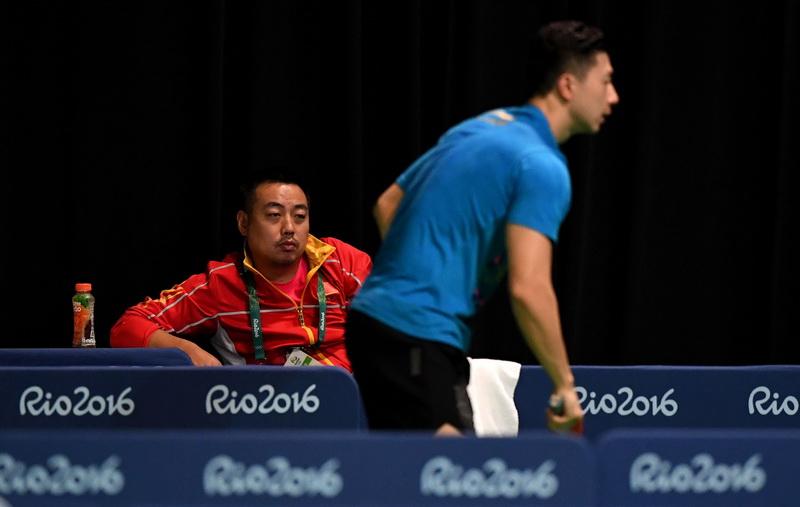 中国乒乓球队总教练刘国梁(左)在观看队员马龙训练
