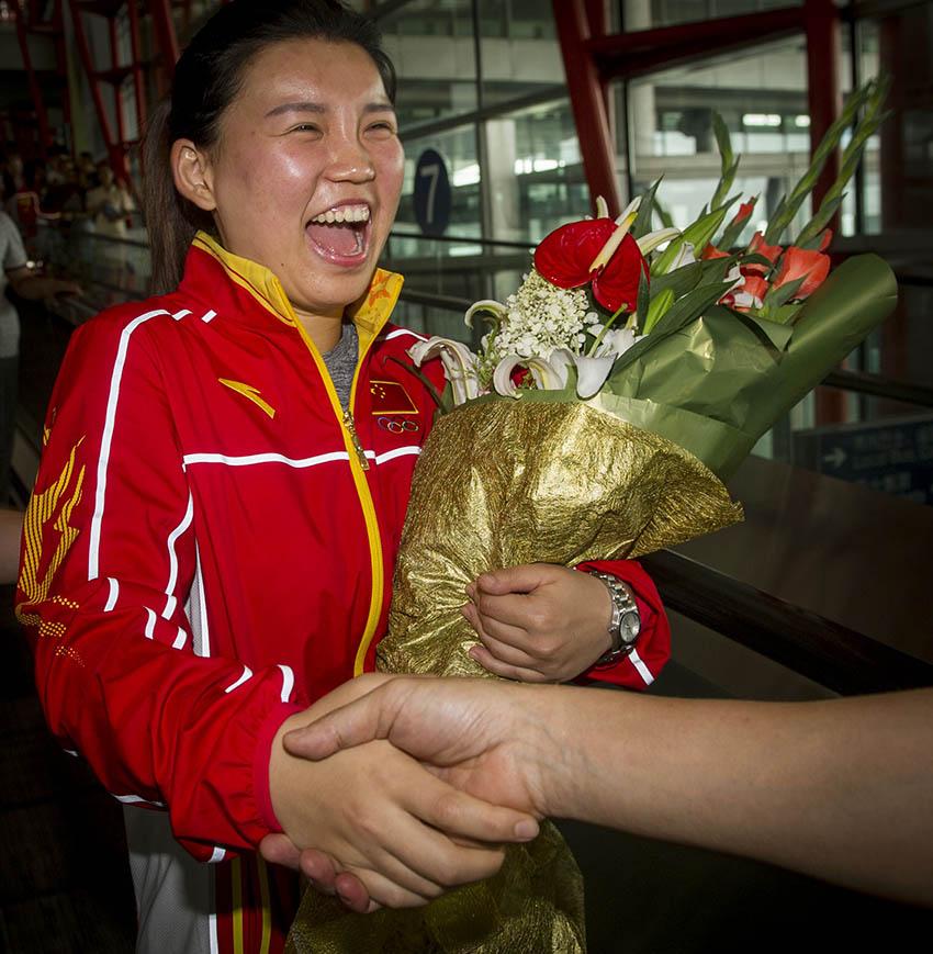 张梦雪在北京首都国际机场手捧鲜花与迎接人员握手