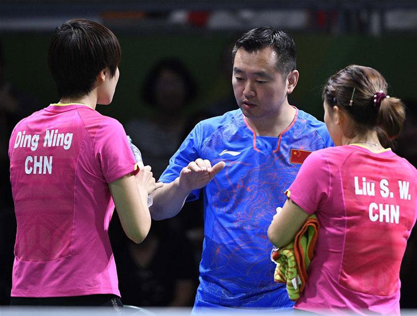 中国队选手刘诗雯(右)/丁宁在比赛中与教练孔令辉交流