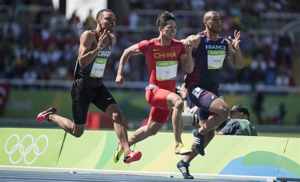 中国选手苏炳添(中)在比赛中