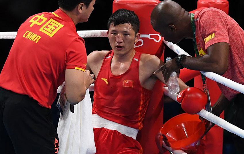 中国选手张家玮(中)在局间休息时接受教练指导