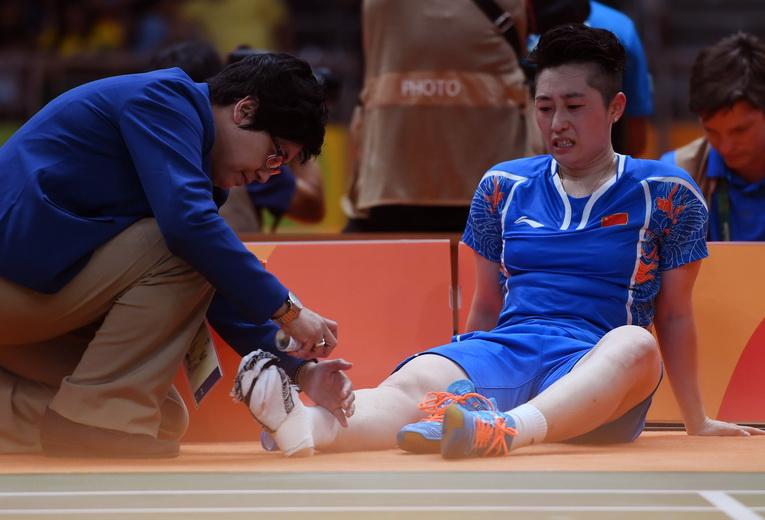 中国队选手于洋(右)在比赛中脚部受伤接受治疗
