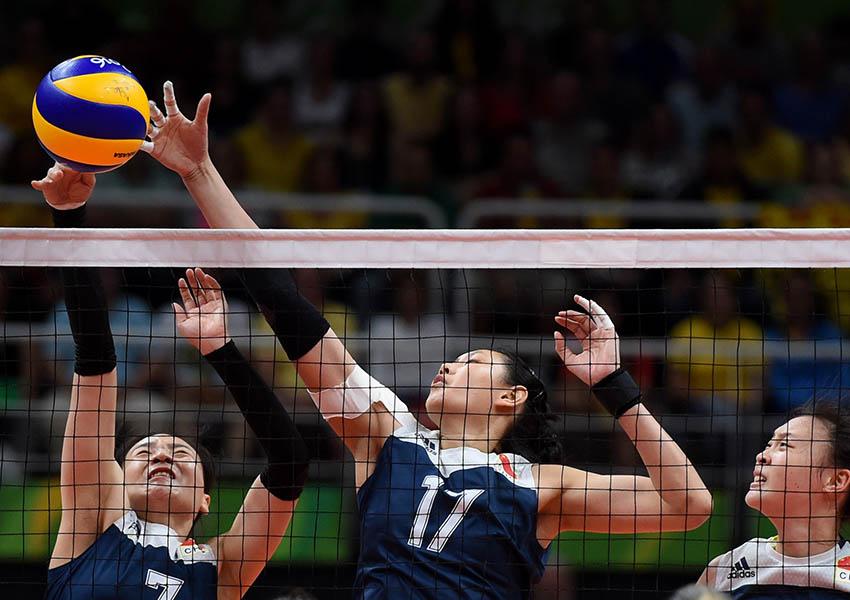 魏秋月(左一)、颜妮(中)在比赛中拦网
