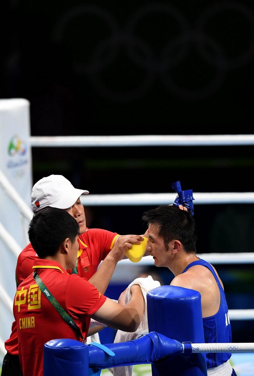 中国选手胡谦逊(右)在比赛间歇处理伤势