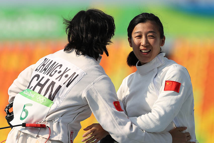陈倩(右)和张晓楠在击剑项目奖励轮对决后拥抱