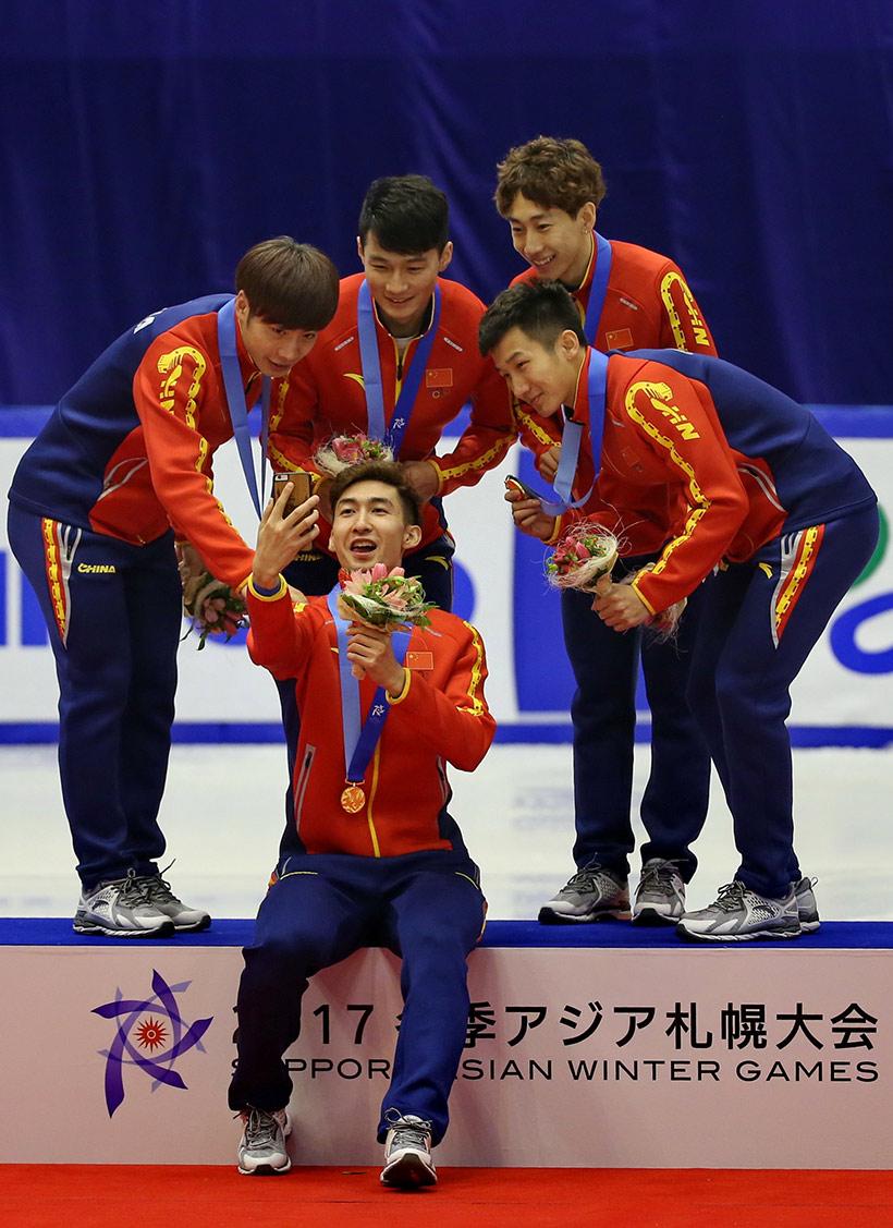 中国队选手武大靖(前)在颁奖仪式后与队友自拍留念。