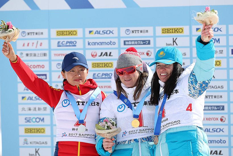 获得女子10公里追逐赛前三名的哈萨克斯坦选手维什涅夫斯卡亚(中)、中国选手张岩(左)和哈萨克斯坦选手达里娅在颁奖仪式上。