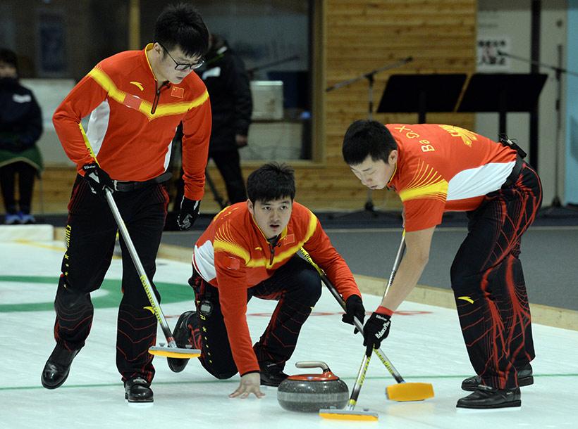 中国队选手徐晓明(中)在比赛中投掷冰壶。