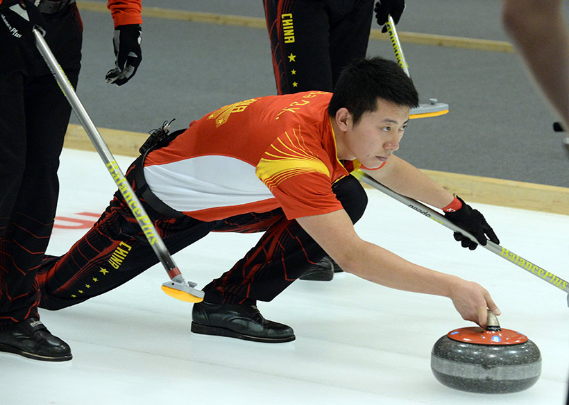 中国队选手巴德鑫在比赛中投掷冰壶。