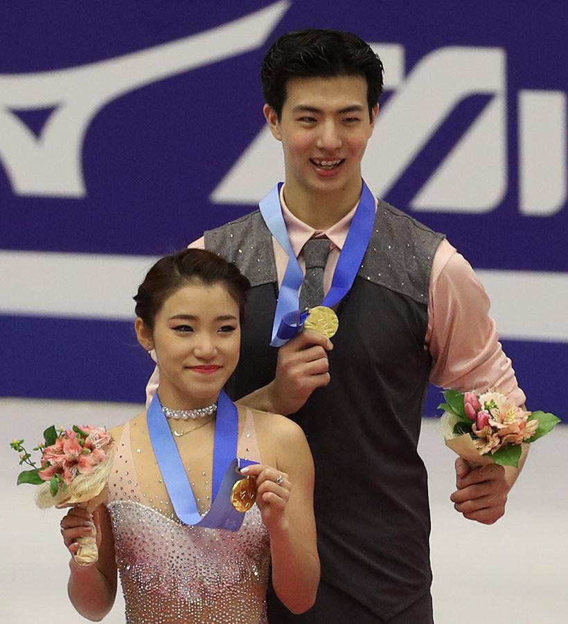 中国选手王诗玥(右)/柳鑫宇在领奖台上展示金牌。