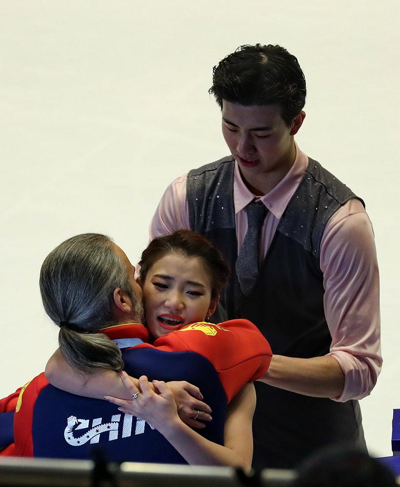 中国选手王诗玥(中)、柳鑫宇(右)在冰舞自由舞比赛结束后与教练拥抱庆祝。