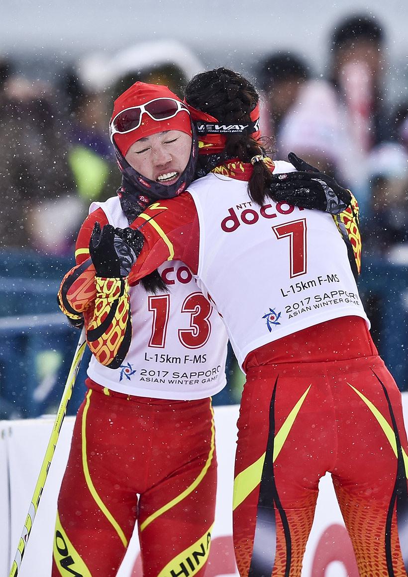 中国队选手李宏雪(左)抵达终点后与队友池春雪拥抱庆祝。