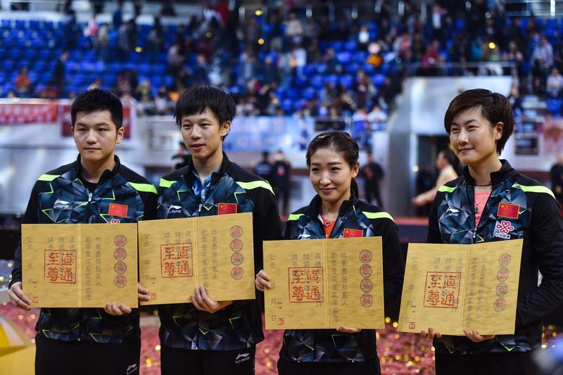 """樊振东、林高远、刘诗雯和丁宁(从左到右)在赛后展示象征直通资格的""""通关文牒"""""""