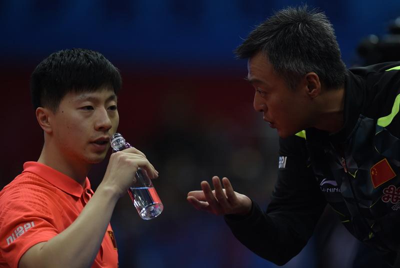 中国男队主教练秦志戬(右)在比赛间隙指导马龙