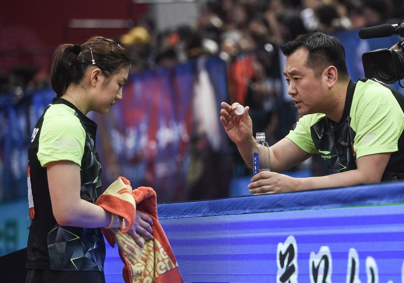 陈梦(左)在比赛中接受教练孔令辉指导
