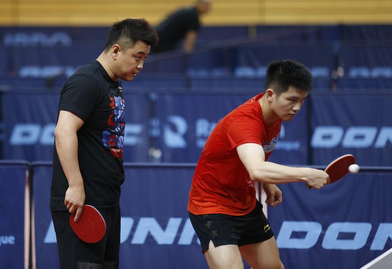 男队教练王皓(左)指导樊振东训练