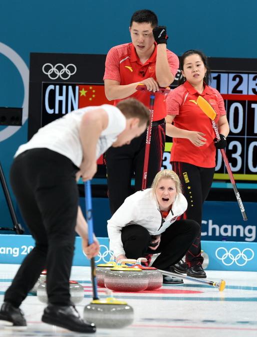中国选手巴德鑫(后左)、王芮(后右)比赛中观察对手的冰壶线路