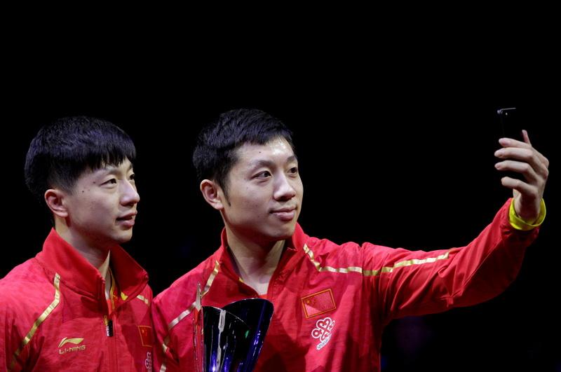中国选手马龙(左)和许昕在颁奖仪式上自拍合影