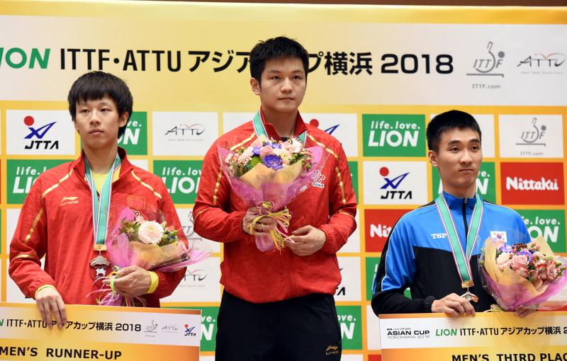 获得冠军的樊振东(中)与亚军林高远(左)、季军韩国选手李尚洙在颁奖仪式上