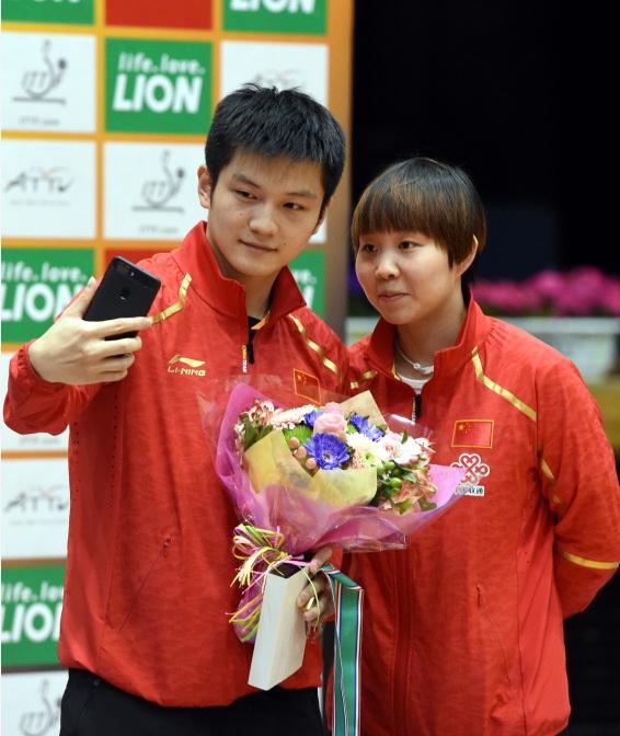 获得男单冠军的樊振东(左)与获得女单冠军的朱雨玲在颁奖仪式后自拍
