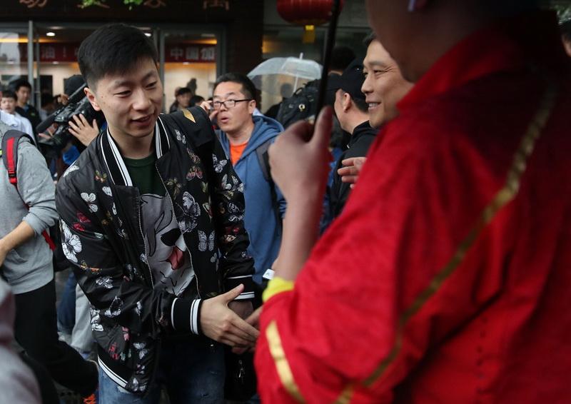 中国乒乓球男队选手马龙(左)与前来送行的人员握手