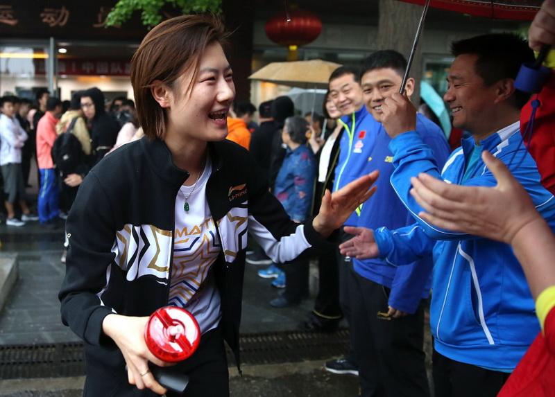 中国乒乓球女队选手丁宁(左)与前来送行的人员击掌