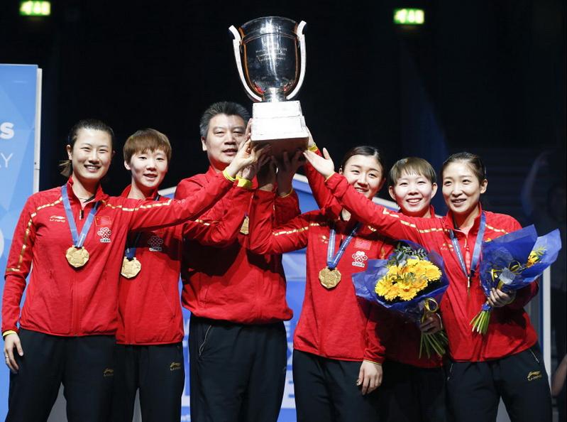 中国队队员和教练李隼(左三)在颁奖仪式上捧起冠军奖杯——考比伦杯