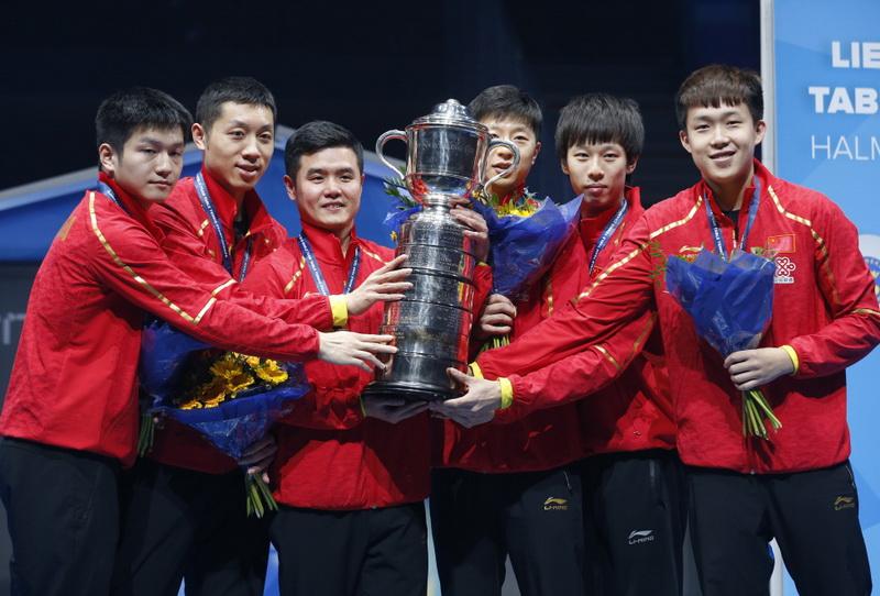 中国队队员和教练刘国正(左三)捧起斯韦思林杯