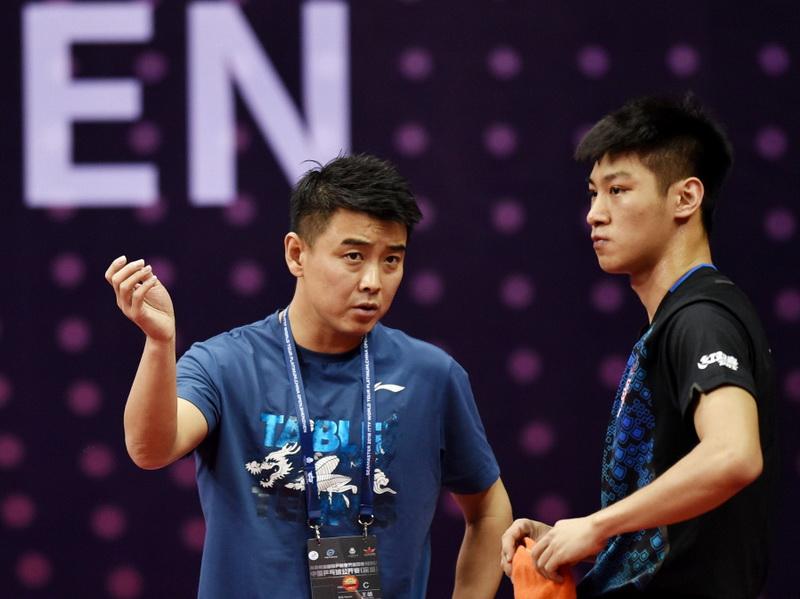 男队教练王皓(左)在比赛间隙指导队员薛飞