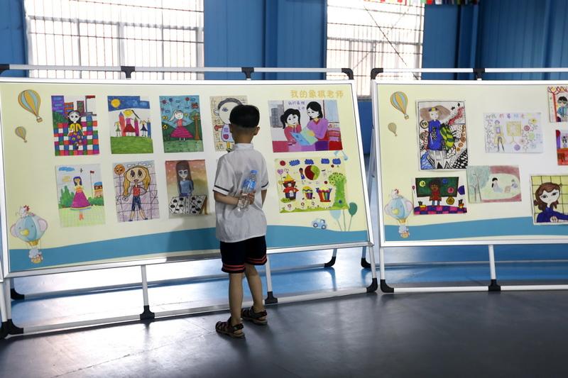 """主赛场参赛的同学们观看""""我的象棋老师""""主题画展"""