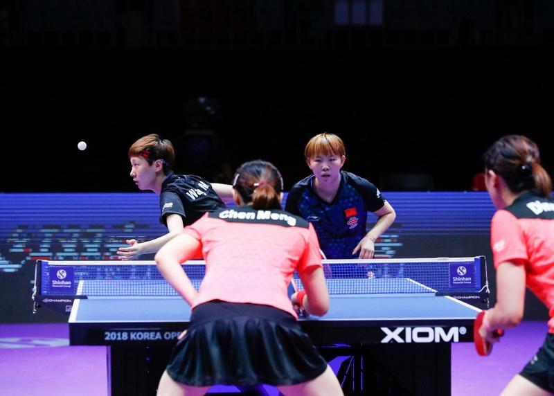王曼昱(后左)在比赛中发球