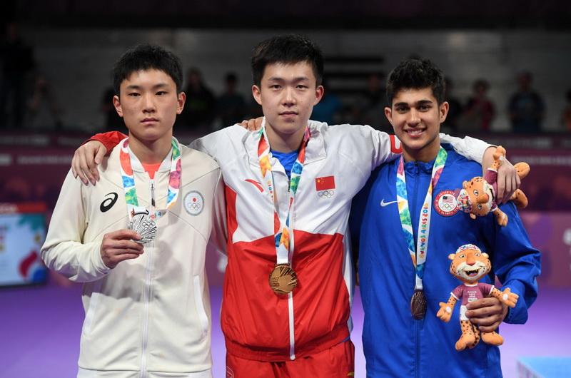 分获冠、亚、季军的中国选手王楚钦(中)、日本选手张本智和(左)、美国选手卡纳克在颁奖仪式后合影