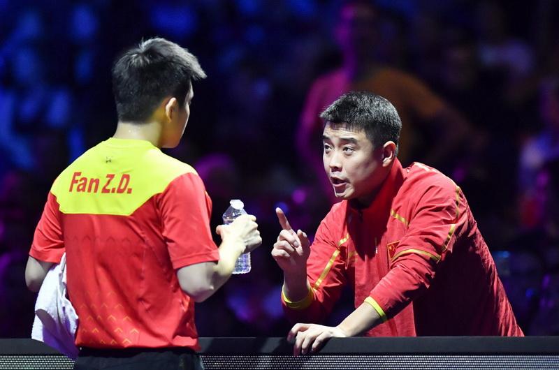 樊振东(左)在比赛间隙接受教练王皓的指导