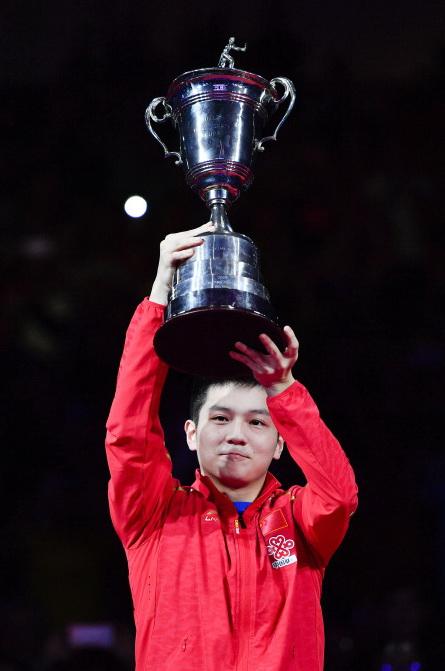 樊振东在颁奖仪式上高举奖杯庆祝